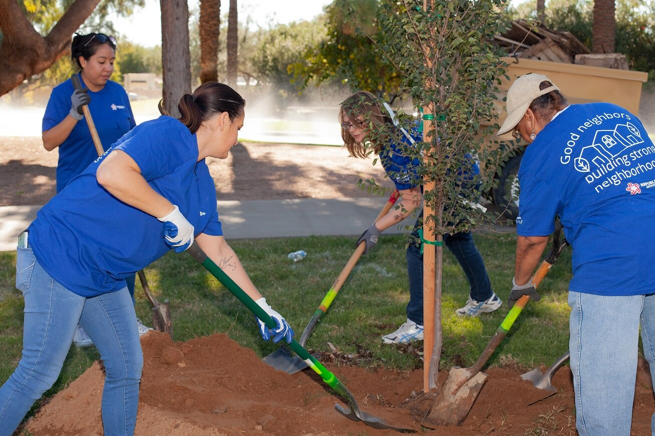 Four volunteers with shovels filling in the hole a tree was planted in
