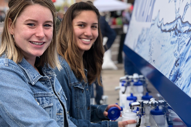 two young ladies filling up water bottles from the scottsdale water truck