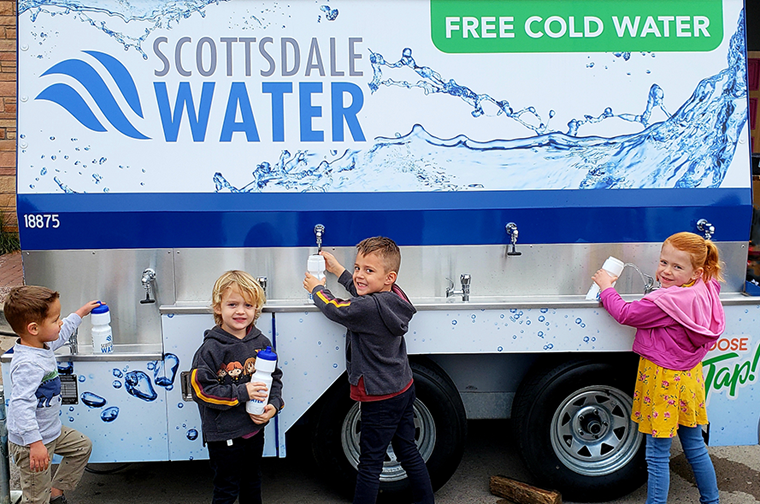 4 children filling up water bottles from the scottsdale water truck